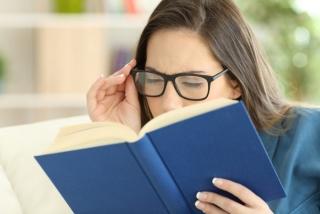 老眼で本を読みづらそうにする女性