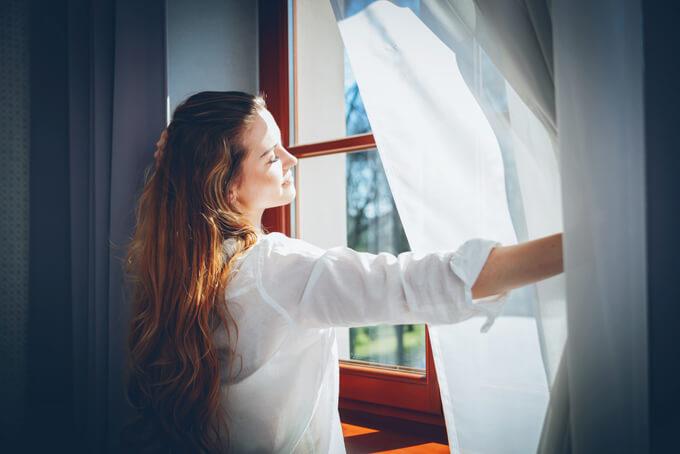 窓を開けようとしている女性の画像