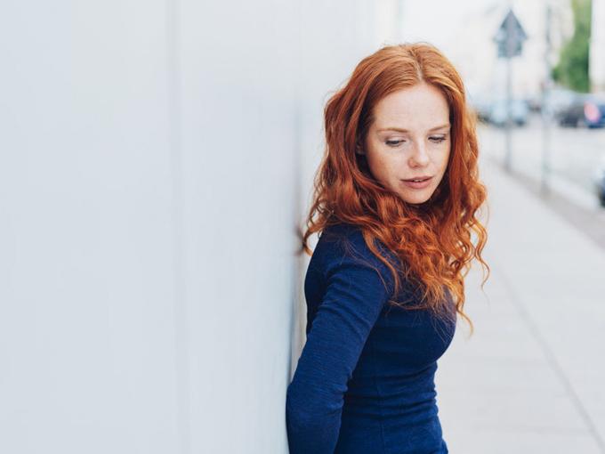 壁の前に立つ女性の画像
