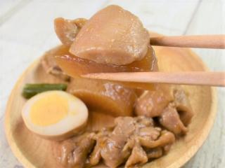 箸で掴んだ「味しみ鶏大根」の画像