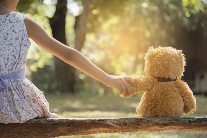 クマのぬいぐるみの手をつかんでいる子供の後ろ姿