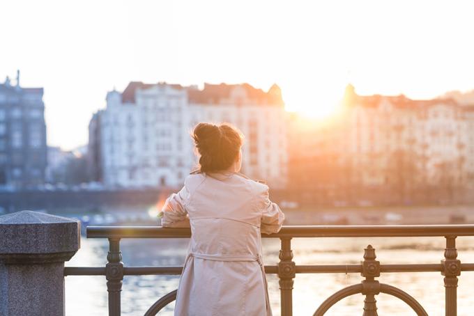夕日を見ている女性の後ろ姿