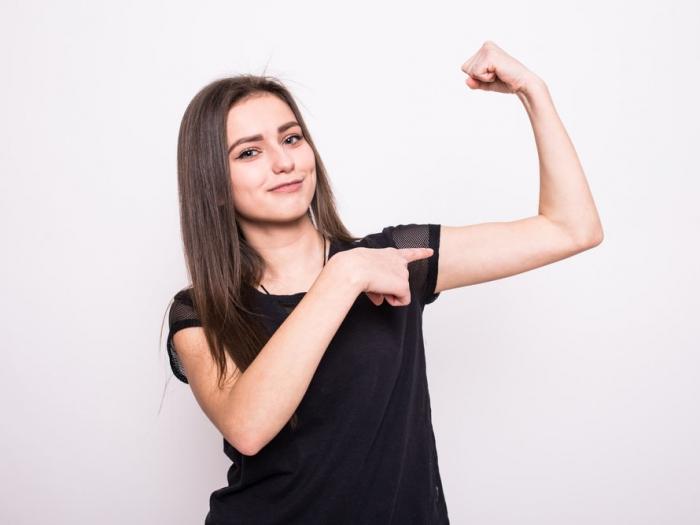 力こぶを作っている女性の画像
