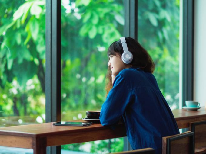 イヤホンで音を聴いている女性