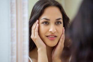 自分の顔を診断している女性