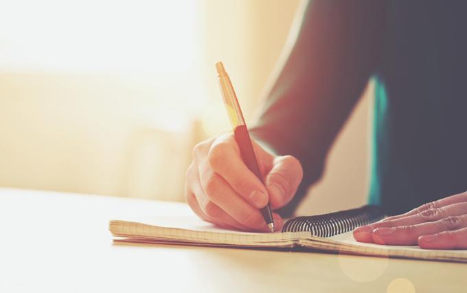 ペンで文字を書いている