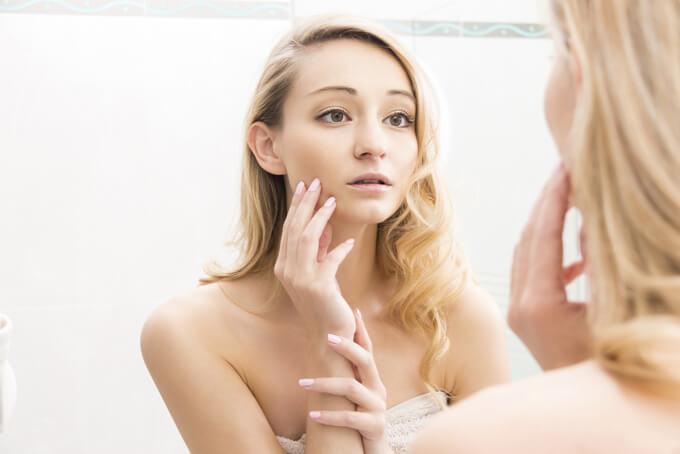 不安げに鏡を見ている女性