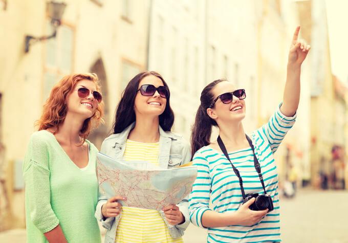 地図を見ながら街を歩いている女性3人