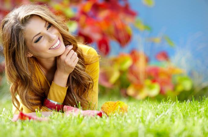 笑顔の女性が芝生の上で横になっている画像