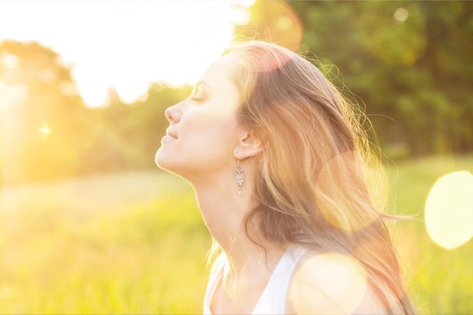 外で日差しを浴びる女性