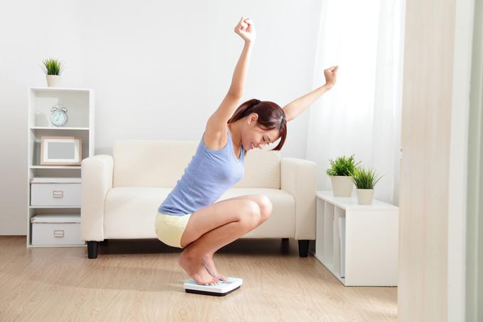 体重計に乗って喜ぶ女性の画像
