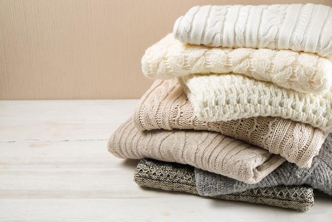 たたんで積まれたセーターの画像