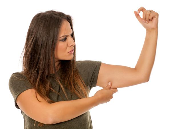 二の腕をつまむ女性の画像