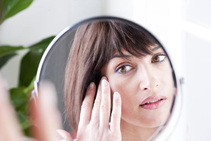 鏡で目元を確かめる女性の画像
