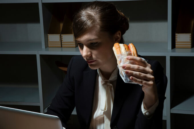 残業中でホットドッグを食べる女性
