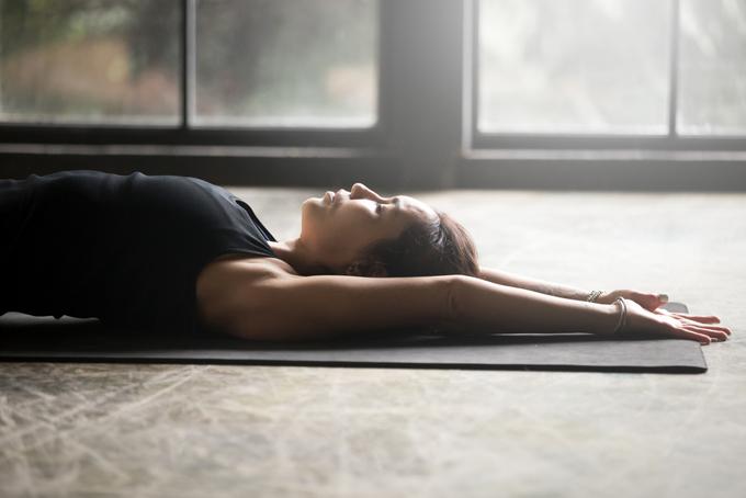 横になり体をゆるめる女性