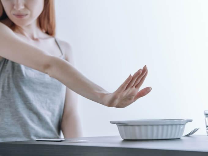 皿を遠ざける女性