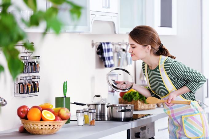 鍋の蓋を開けて匂いを嗅いでいる女性の画像