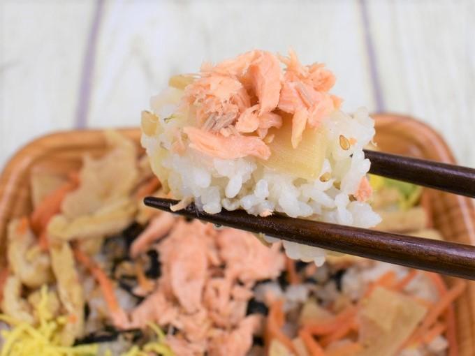 「鮭とたけのこのごはん(スーパー大麦入り)」を箸で持ち上げている画像