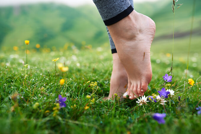 草むらで素足で歩く女性