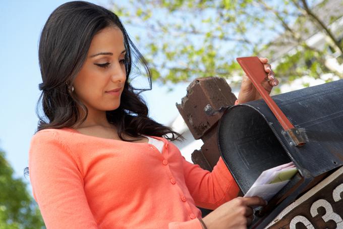 手紙をチェックする女性のイメージ画像