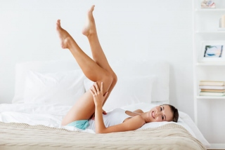ベッドの上で両脚をあげている女性