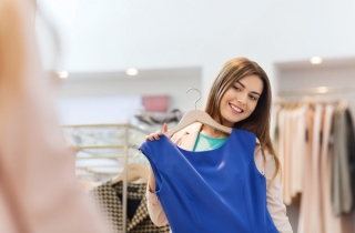 青い服を体に合わせる女性の画像