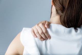 肩を押さえている女性の画像