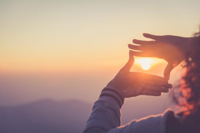 手から太陽をのぞいている