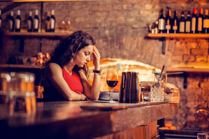 お酒を飲んで頭が痛くなっている女性