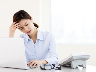 デスクの上で頭を押さえる女性の画像