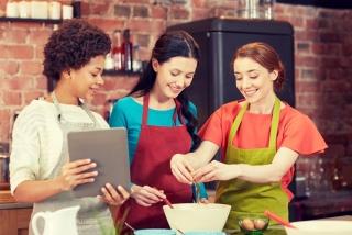 レシピを見ながら料理を作る3人の女性の画像