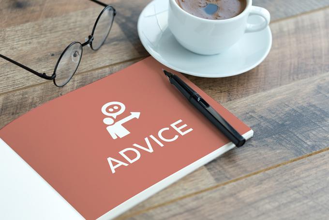 机の上にメガネとコーヒー、アドバイスと書かれたノート