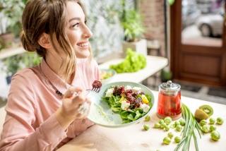 器を持って食事をしている女性の画像