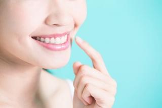 真っ白の歯を指さしている女性の画像