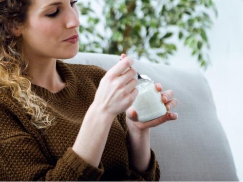 女性が小カップとスプーンを持っている写真
