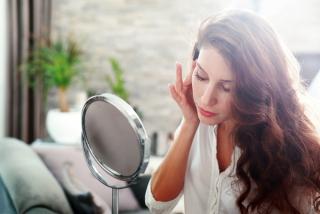 鏡を見ながら顔をチェックしている女性の画像