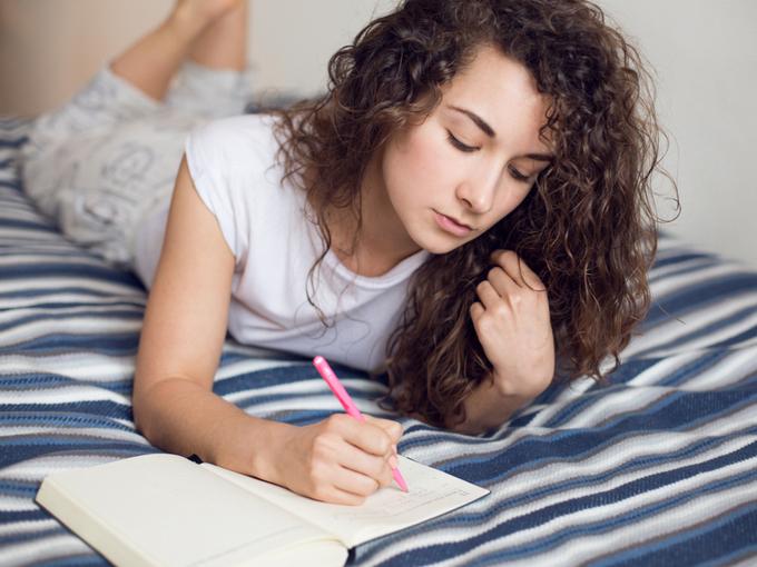 女性がベッドで日記を書いている画像