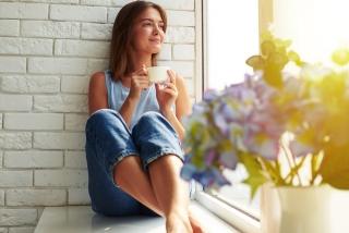 女性が窓辺でゆっくりお茶を飲んでいる