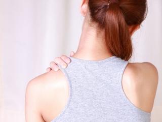 肩を押さえる女性の後ろ姿の画像
