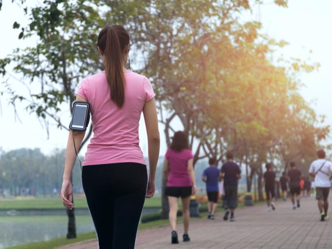 スマホを装着して歩いている女性の画像