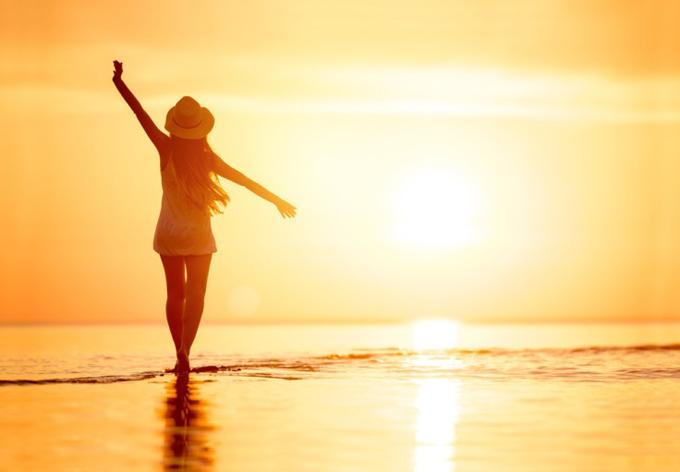 海辺で太陽を見ながらのびをする女性