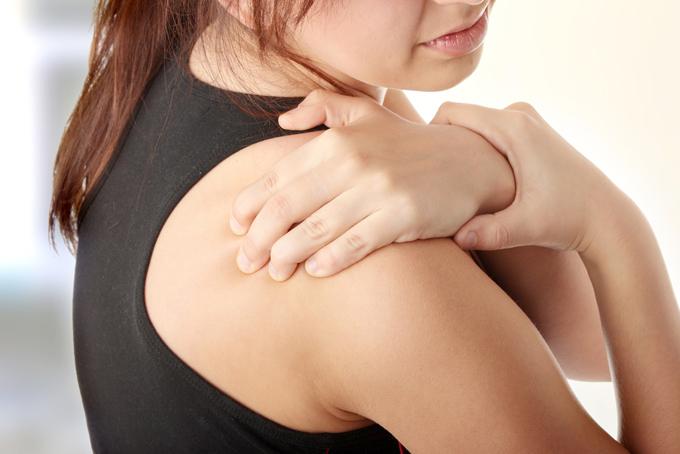 肩を押さえる女性の画像