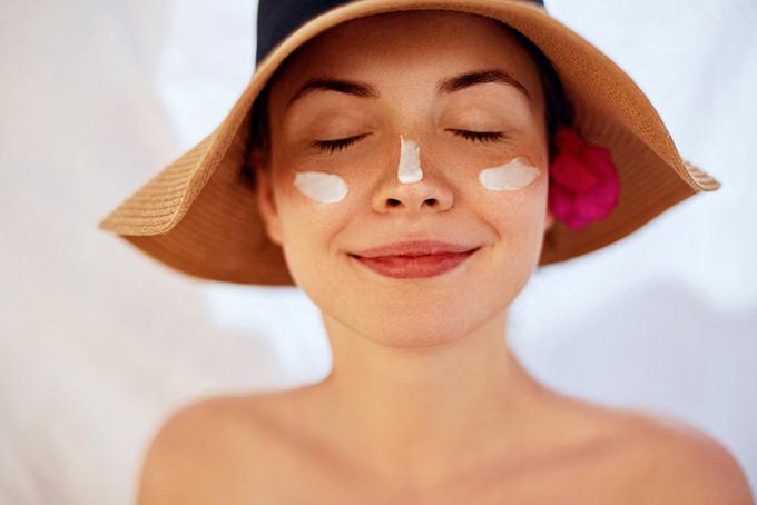 日焼け止めを顔に乗せた女性の画像