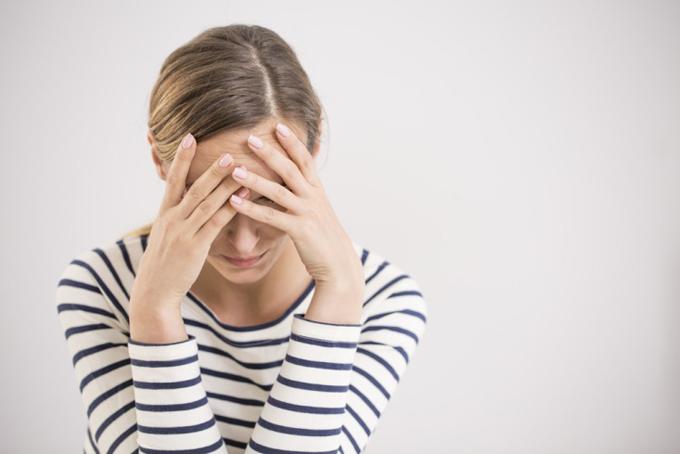 頭痛でやる気がなくなっている女性