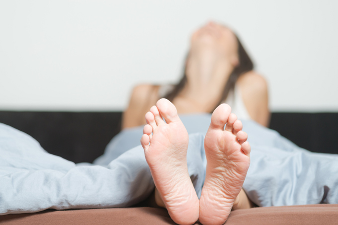 ベッドに横になる女性の足裏