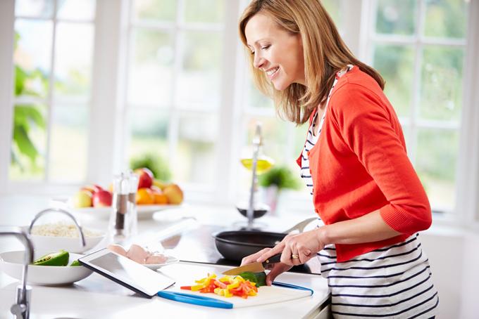 キッチンでレシピを見ながら料理をする女性の画像