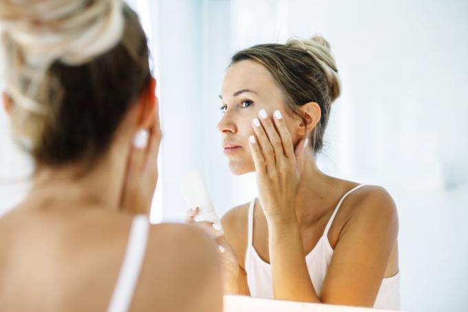 肌を鏡をみながらチェックする女性