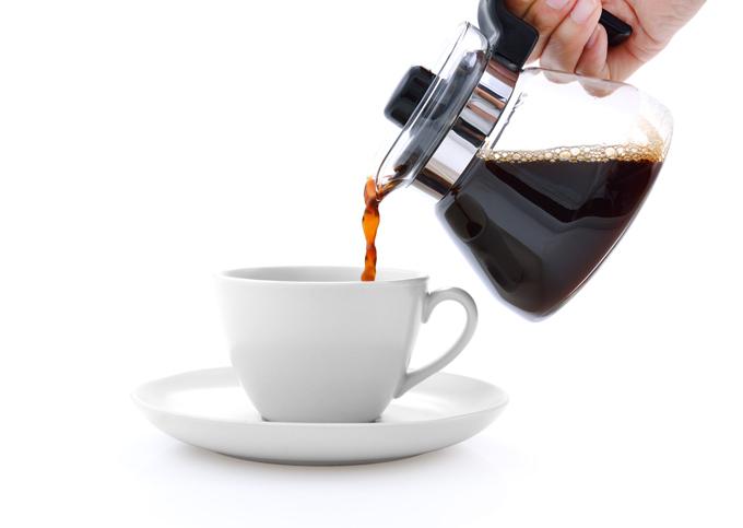 コーヒーカップにコーヒーを注いでいる画像