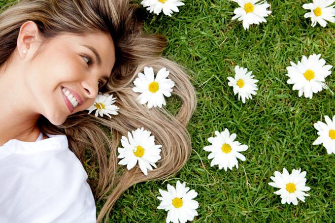 芝生に寝転んでお花に囲まれる女性
